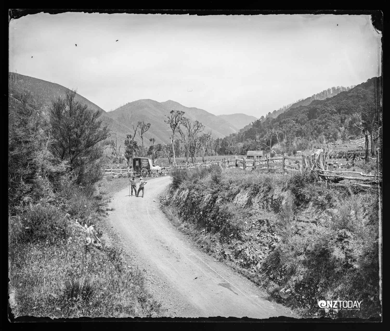 Featherston side of the Remutaka [Rimutaka] Hill, from the cutting at Cave's Bridge. Two men are standing at the bend on a road which passes through fenced farmland on either side. Bragge's photography cart is parked behind the men at the side of the road