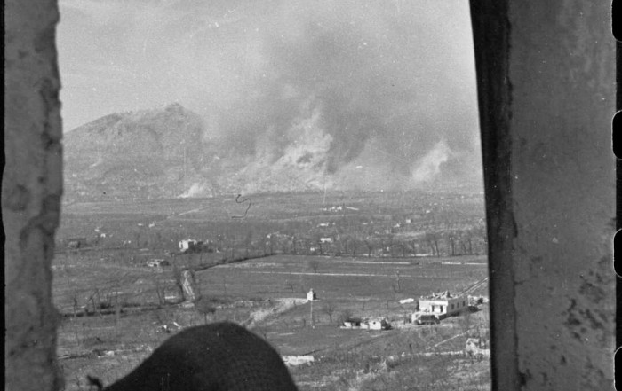 A New Zealand observer silhouetted against the battle area at Monte Cassino, Italy, with the bursts of shells and bombs obscuring the town. Photograph taken on 15 March 1944 by George Frederick Kaye