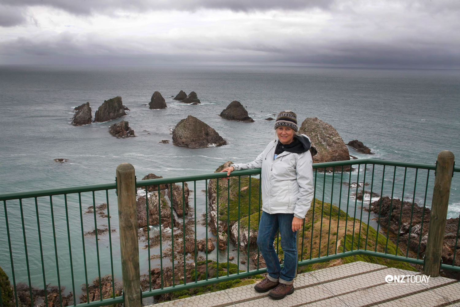 Black clouds are skimming the horizon behind me at Nugget Point