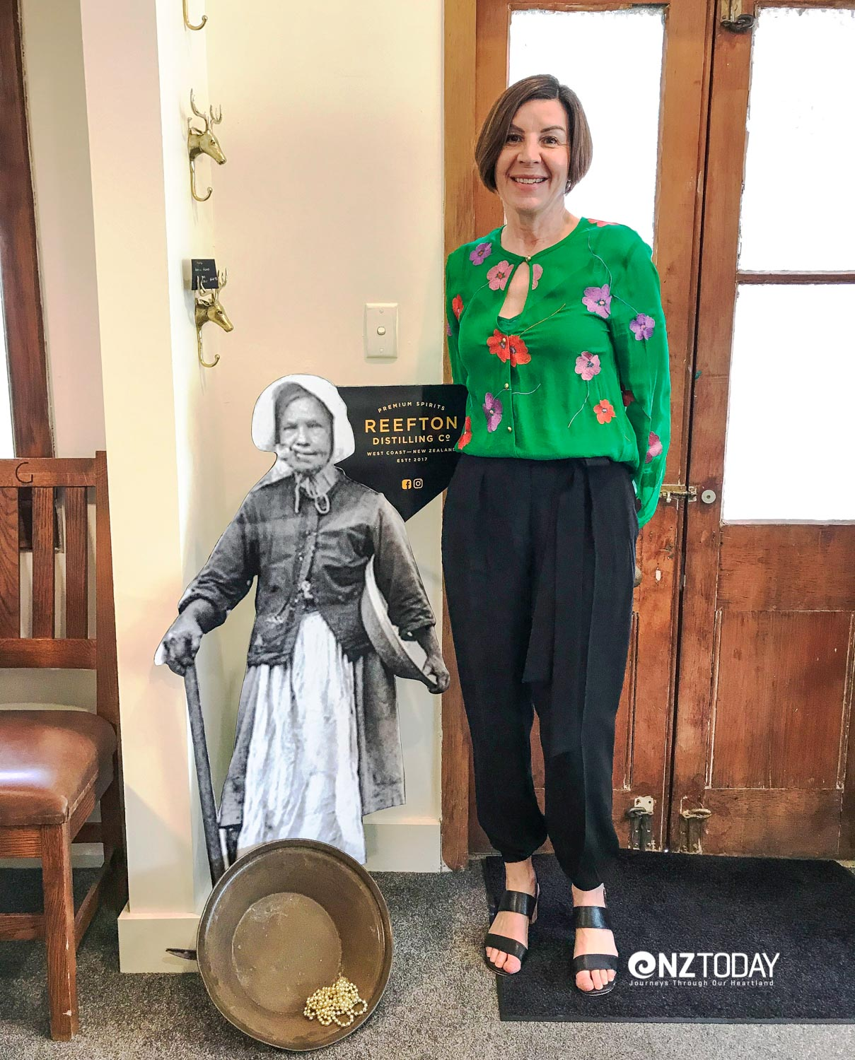 Patsy Bass, Managing Director, Reefton Distilling Co. stands alongside an image of Bridget Goodwin, 'Little Biddy'